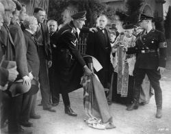 Figure 3. Reinhard Heydrich (John Carradine) uses a sacred cloth to wipe his boots to provoke the priest (Al Shean) in Hitler's Madman. (Photo copyright 1943 United Artists Corp.; courtesy of the Museum of Modern Art)