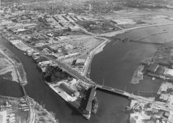 Figure 3. Mixed use of the Benton Harbor/St. Joseph waterfront, circa 1960. The Graham and Morton passenger/freight terminal sits at the lower center of this photograph—at the confluence of the Benton Harbor Canal and St. Joseph River—flanked by open storage docks and a marina/boat repair facility formerly occupied by Robinson Marine (a St. Joseph boatbuilding company). To the left of the water tower sits the nationally renowned Benton Harbor Fruit Market, now relocated closer to U.S. Interstate 94. Courtesy of the Herald-Palladium.