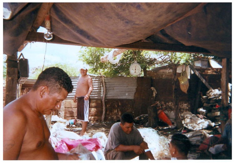Figure 4. Group of extended family members cleaning and sorting recyclables. Taken in the courtyard of a residence in La Chureca, photo shows churequeros cleaning intravenous IV tubing and shoe soles to be categorized and sold to a recycling factory. (Source: photograph courtesy of J.P., waste site resident).