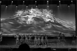 Figure 4. The Hindu myth of the churning of the Sea of Milk in Smile of Angkor. In the foreground male performers portray gods and demons engaged in a tug of war that churns the sea to bring forth the apsaras (moving images on the screen).<br/><br/>(Photo: Celia Tuchman-Rosta)