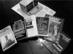 Figure 5. A selection of 1980s trade books written as guides to home computers and video games, whose diverse and notable authors include Martin Amis, Michael Crichton, Newt Gingrich, Frank Herbert, Hugh Kenner, and Jerry Pournelle; also a 1984 pop-up book entitled Inside the Personal Computer.<br/><br/>Photo by Kirschenbaum.