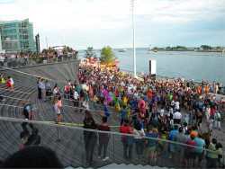 Figure 2. Planet Chicago. Chicago Samba dancers ascend a staircase at Navy Pier on August 26, 2016, as the Planet Chicago procession arrives at a stage (far right) where the Natya Dance Theatre is about to perform. Image courtesy of the author.