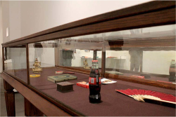 Figure 7. Arahmaiani, Etalase, 1994. Display case containing personal photograph, icon, Coca-Cola bottle, Al-Qur'an, fan, Patkwa mirror, drum, box of sand, and pack of condoms, 95 × 147 × 67 cm. Image courtesy of the artist