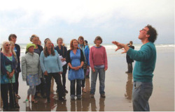 "Fig. 14. Choir master Nick Jones leads Côr y Gors community choir in song on the shoreline at Borth; image by Becky Payne. Beckyfleming, ""Pictures from the Cymerau Launch,"" Hydrocitizens (blog), October 10, 2015, ."